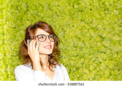 Businesswoman talking on the phone near the green wall, wearing glasses