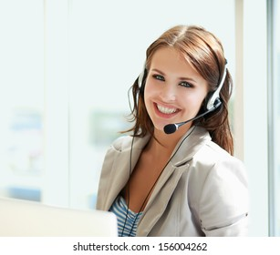 businesswoman talking on the phone while working on her computer at the office