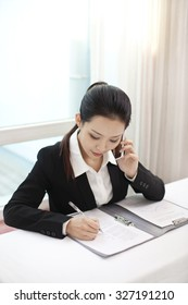 Businesswoman talking on the phone while signing documents