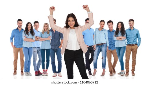 businesswoman team leader celebrating victory with both hands in the air, with her young casual group while standing on white background in front of them.
