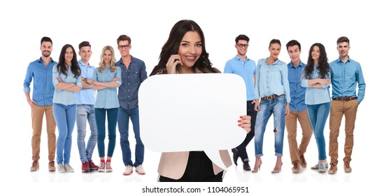businesswoman team leader holds empty bubble speech while talking on the phone and standing on white background in front of her young casual team