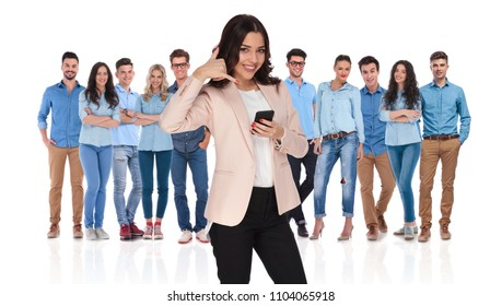 businesswoman team leader with phone wants you to call her young casual group who is standing behind her on white background. She is making the call us sign with her hand.