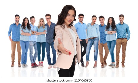 businesswoman team leader welcomes you with a warm handshake and a smile in her young casual group while standing on white background