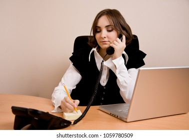 Businesswoman with telephone sitting at  the chair at office
