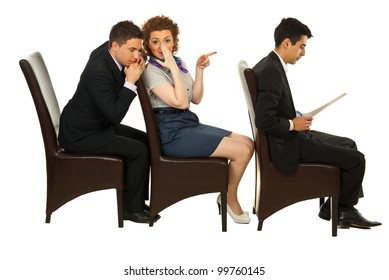 Businesswoman telling secret about first colleague man on chair to business an who listening her with closed eyes  and sitting all in a row on chairs