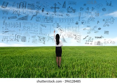 Businesswoman thinking with business plan on meadow