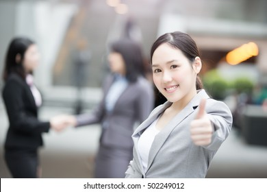 businesswoman thumb up and smile to you in hongkong