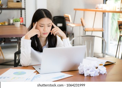 Businesswoman tired and stressed with overworked at desk, woman asian with worried not idea with graph analysis laptop and crumpled paper at office, freelance and business concept.
