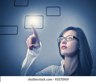 Businesswoman touching a button on a touchscreen
