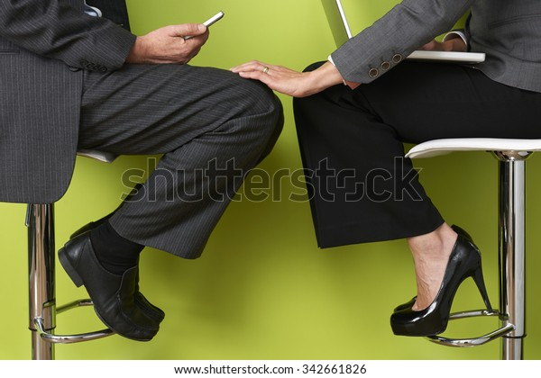 Businesswoman Touching Colleague's Leg