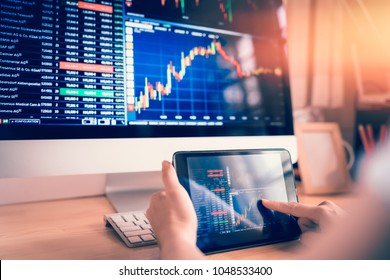 Businesswoman trading stocks with tablet and graph Analysis in desktop computer