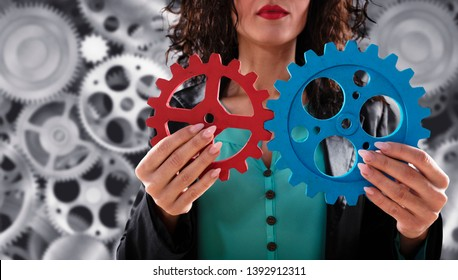 Businesswoman tries to connect gears pieces. Concept of Teamwork, partnership and integration.