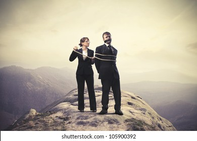 Businesswoman tying tight a businessman on a mountain peak