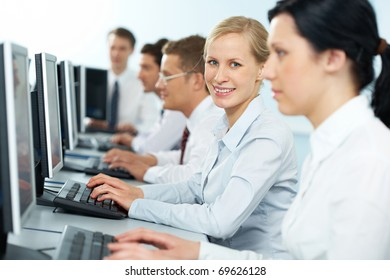 A businesswoman typing among her colleagues, looking at camera and smiling