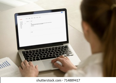 Businesswoman typing e-mail on laptop at office desk, composing professional email letter using business etiquette, writing e message to corporate client online, focus on screen, close up rear view