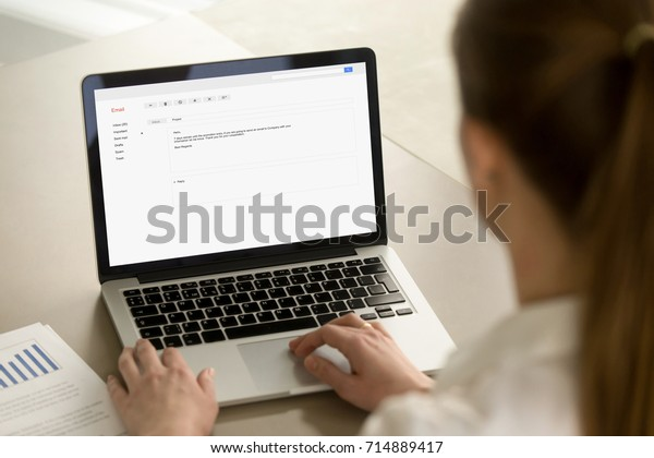 オフィスのデスクでノートパソコンに電子メールを入力し、ビジネスエチケットを使用してプロの電子メールレターを作成し、企業のクライアントに電子メールをオンラインで書き込み、画面にフォーカスし、背面を接写