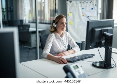 Businesswoman typing on a computer keyboard in an office.