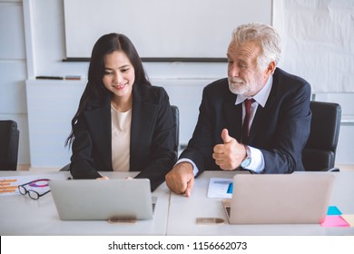 Businesswoman  typing on laptop. Beautiful young asia woman sitting together with her old white man boss discuss business plan. Cross generation business team concept.