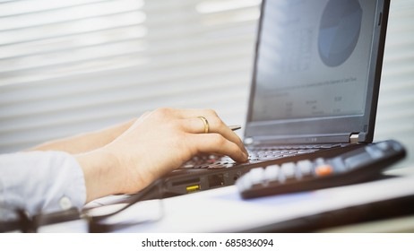 Businesswoman typing on a mobile computer at an office desk. Shallow DOF, focus on the computer.