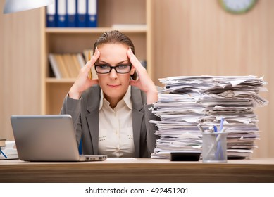 Businesswoman under stress from too much work in the office