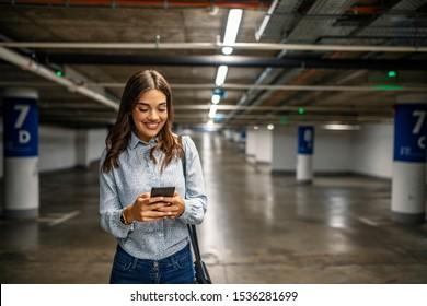 Businesswoman in underground garage. Elegant woman using smartphone in parking garage. Fashionable young woman texting on smartphone. Businesswoman in a parking garage