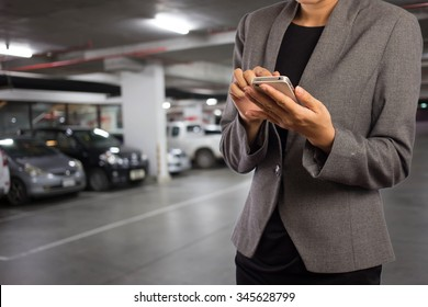 Businesswoman in Underground parking with cars.