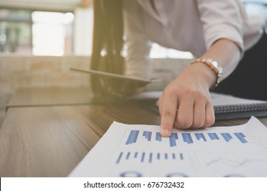 businesswoman use tablet to analyze market chart at workplace.  young female entrepreneur woman working with business document at office. analytic financial accounting graph plan report.  paperwork