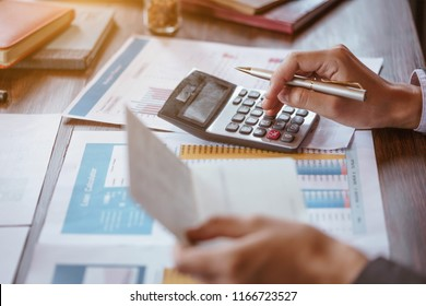 Businesswoman using calculator to calculate saving account passbook and statement with financial report.Female accountant or banker use calculator. Savings, finances and economy concept.