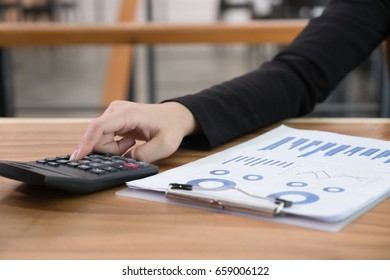businesswoman using calculator at workplace.  young female entrepreneur woman working with business document at office. analytic financial accounting market chart and graph plan report.