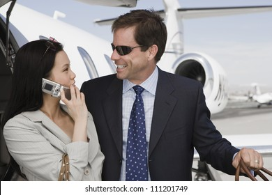 Businesswoman using cell phone while looking at businessman with airplane in background