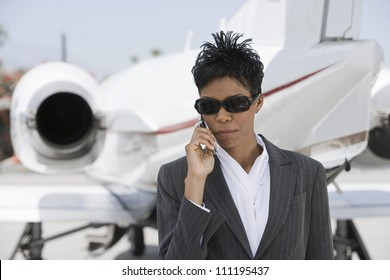 Businesswoman using cellphone with airplane in background