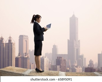 Businesswoman using computer and  stand on the top of a skyscraper with cityscape