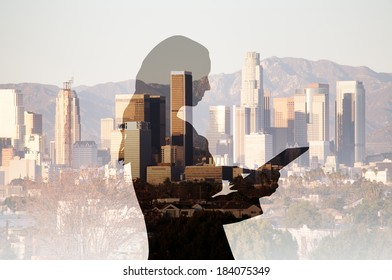 Businesswoman using a computer tablet composited with a cityscape of Los Angeles