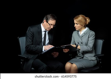Businesswoman using digital tablet and looking at businessman signing papers isolated on black