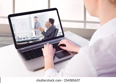 Businesswoman using her laptop against business people in office at presentation