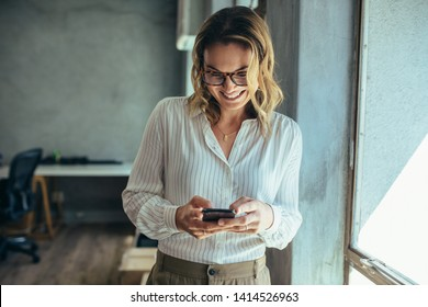 Businesswoman using her smart phone in office. Female entrepreneur looking at her mobile phone and smiling. Reading text messages. - Shutterstock ID 1414526963