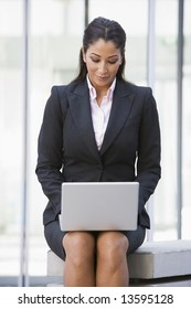 Businesswoman using laptop computer outside office