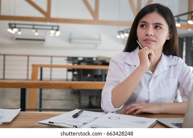 businesswoman using laptop computer at workplace.  young female entrepreneur woman working with business document analyze graph and chart at office. Marketing plan researching. Paperwork on table.