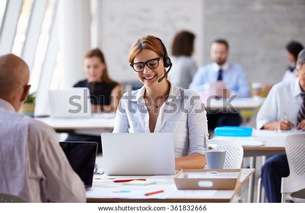 Businesswoman Using Laptop In Customer Service Department