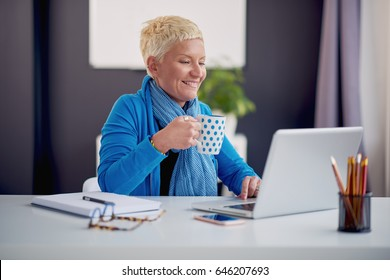 Businesswoman using laptop and drinking coffee while sitting in modern office