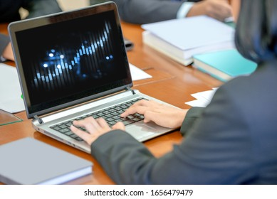 Businesswoman using a laptop with the financial chart in screen on the workplace