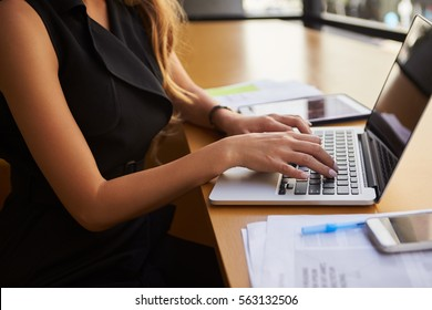 Businesswoman using laptop in office, mid section, side view