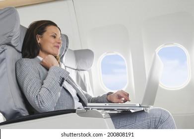 Geschäftsfrau mit Laptop im Flugzeug