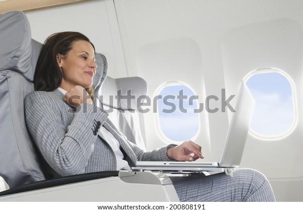 Businesswoman using laptop on airplane