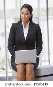 Businesswoman using laptop outside office