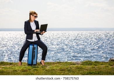 Businesswoman using laptop at seaside