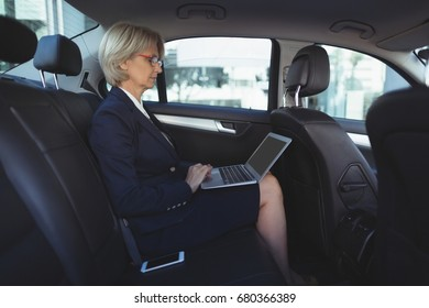 Businesswoman using laptop while traveling in car