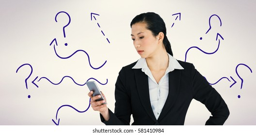 Businesswoman using mobile phone against grey background