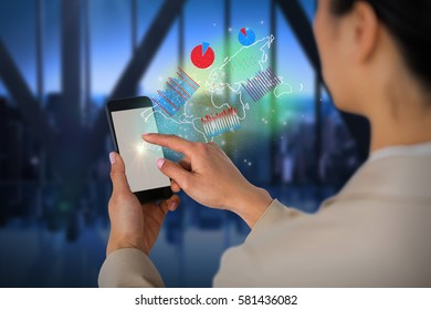 Businesswoman using mobile phone against room with large window looking on city