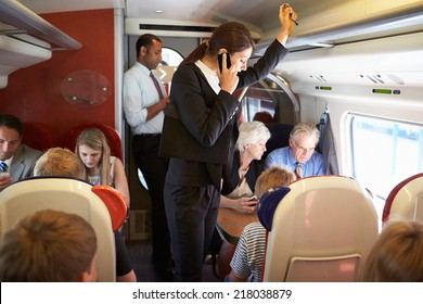 Businesswoman Using Mobile Phone On Busy Commuter Train